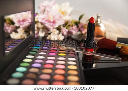 makeup kit lipstick flowers - stock photo