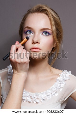 Makeup. Make-up Applying closeup. Cosmetic Powder Brush for Make up. Perfect Skin. Nude Lipstick. Isolated on a rey Background. Makeover - stock photo