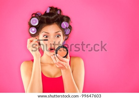 Makeup mascara woman with hair rollers getting ready looking in pocket mirror. Funny image of beautiful trendy young mixed race asian caucasian female fashion model putting makeup on pink background. - stock photo