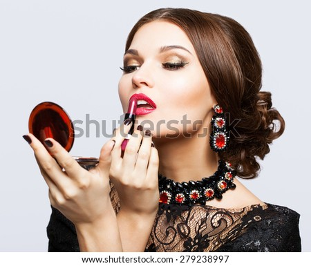 Makeup of young beautiful brunette woman in black dress on gray background with lipstick and mirror in hands - stock photo