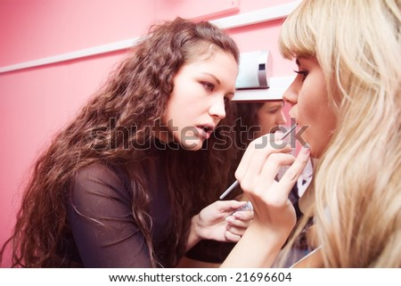 Makeup professional at work. Focus on hand. - stock photo