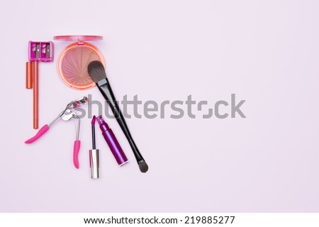 makeup set consisting of a rouge, a brush, a eyelash curler, a lip liner, a sharpener and a pink gloss, isolated on a pink background - stock photo