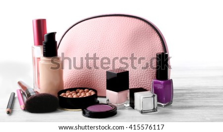 Makeup set with beautician, brush and cosmetics on light background - stock photo