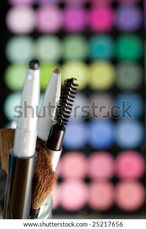 Makeup set with colorful eye shadows as background. - stock photo