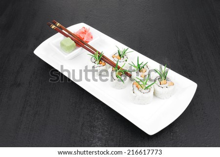 Maki Sushi - California Roll with Cucumber , Cream Cheese and Salmon inside. Served with wasabi and ginger . on long white plate over black table - stock photo