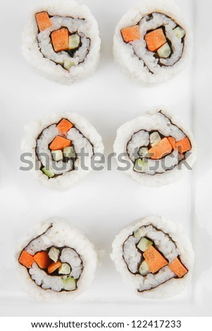 Maki Sushi - California Sushi Roll with Avocado, Cream Cheese and Raw Salmon inside. With wasabi . isolated over white background on square plate - stock photo