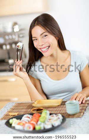 Maki sushi. Healthy lifestyle woman about to eat sushi. Mixed race pretty young woman holding chopsticks smiling happily and cheerful. Full sushi plate in front - stock photo