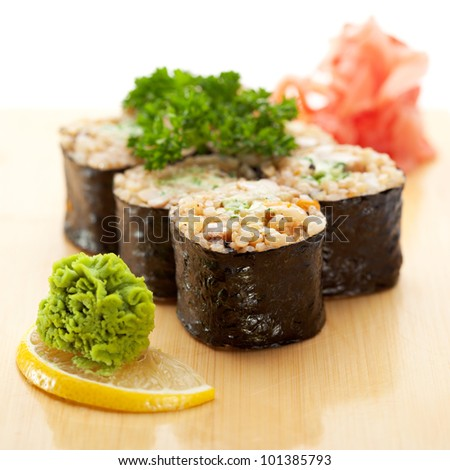 Maki Sushi - Roll with Brown Rice and Green Lettuce inside. Garnished with Ginger and Wasabi - stock photo
