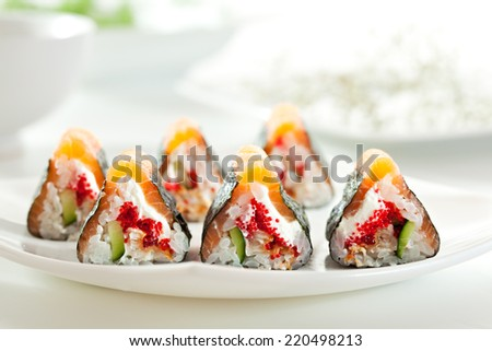 Maki Sushi - Sushi Roll with Cucumber, Tamago, Salmon Roe, Tobiko and Cream Cheese inside. Nori outside. Topped with Salmon - stock photo