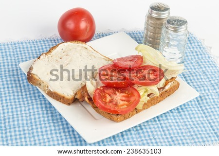 Making a bacon lettuce and tomato sandwich on twelve grain bread.  White plate on blue gingham background. - stock photo