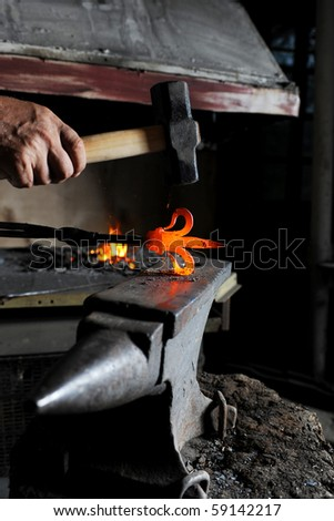Making a decorative pattern in the smithy on the anvil - stock photo