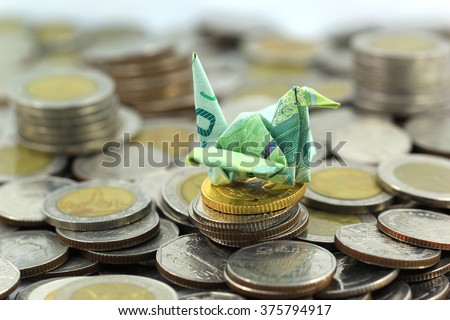 Making a origami bird Thai banknote and coin on white background - stock photo