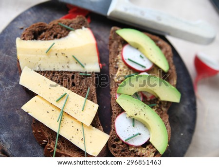 Making a sandwich on dark bread with Gouda cheese, avocado, radishes, whole-grain mustard, chives and black pepper - stock photo