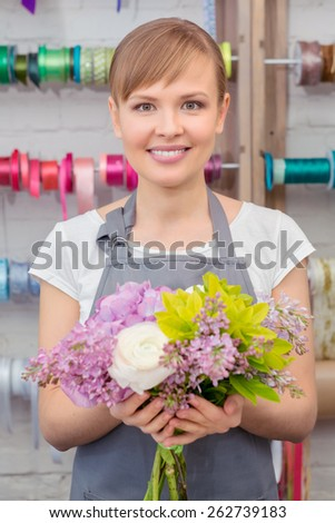 Making a success of her skills. Young smiling florist showing a pretty floral bouquet being completed  - stock photo