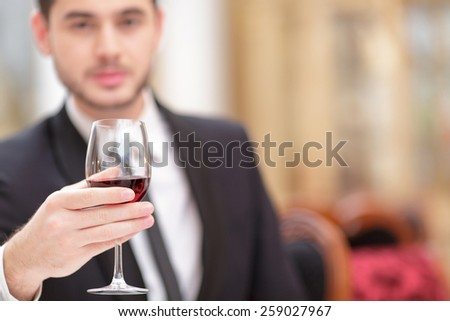 Making a toast. Handsome young man in suit raising his glass of wine while making a toast in luxury restaurant with selective focus - stock photo