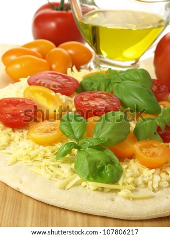 Making a vegetarian pizza with cherry tomatoes - stock photo