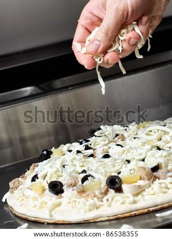 Making an Italian style pizza at kitchen - stock photo