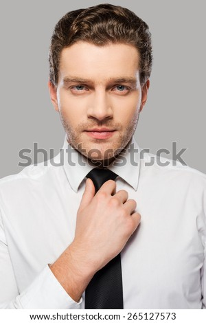 Making business look good. Confident young man in shirt and tie adjusting his necktie and looking at camera while standing against grey background - stock photo