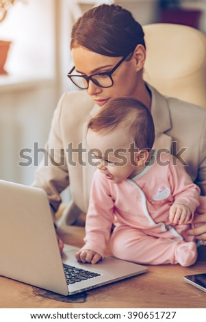 Making business plan with mommy. Little baby girl using laptop while sitting on office desk with her mother in office - stock photo