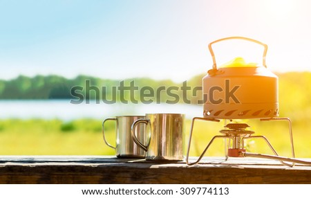 Making coffee or tea on a gas burner on the nature. - stock photo