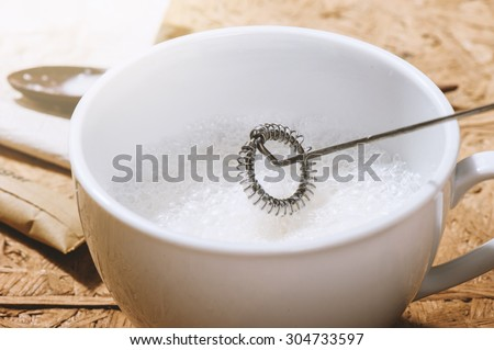 making foamy milk with milk frother - stock photo