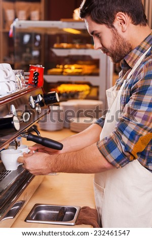 Making fresh coffee. Side view of confident barista making coffee while standing at the bar counter near the coffee machine - stock photo
