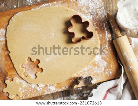 Making gingerbread cookies. Christmas baking background dough and cookie cutters. - stock photo