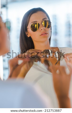 Making her final choice. Beautiful young woman choosing sunglasses to buy while standing in front of the mirror in the optic store  - stock photo