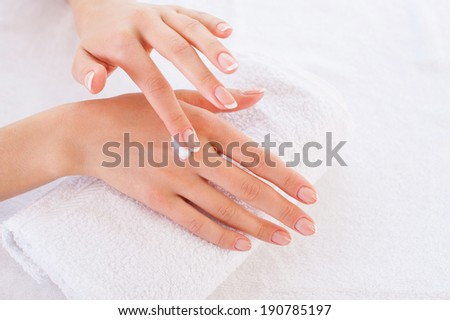 Making her skin clean and smooth. Close-up of woman applying cream on hand - stock photo