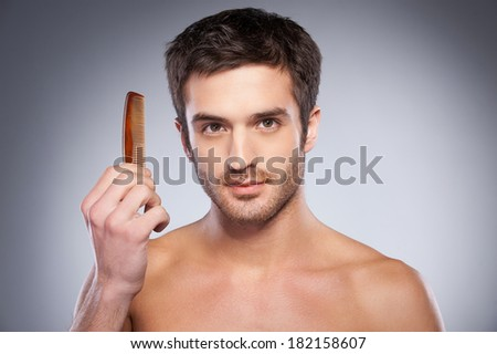 Making his unique style. Handsome young shirtless man holding a comb and looking at camera while standing against grey background - stock photo