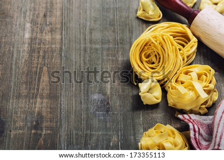 Making homemade pasta on wooden table - stock photo