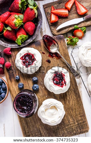 Making homemade pavlova dessert with berry fruits, view from overhead, on wooden kitchen table - stock photo