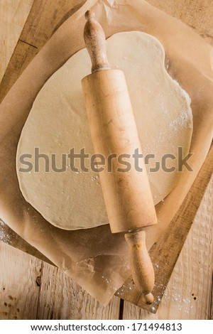 Making homemade pizza in a country kitchen with an overhead view of rolled out dough for the base with a wooden rolling pin on oven paper on an old wooden chopping board - stock photo