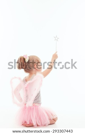 Making magic. Pleasant little girl holding her hand up and keeping wand while sitting  turned backwards on the floor. - stock photo