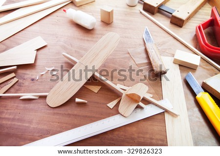 Making model airplane from wood. Wooden air plane handcrafted with balsa wood, on work table by the window. Airplane, knife, balsa wood material and glue on table. - stock photo