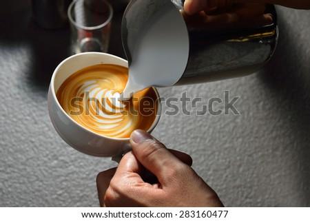 Making of cafe latte art, leaf shape - stock photo