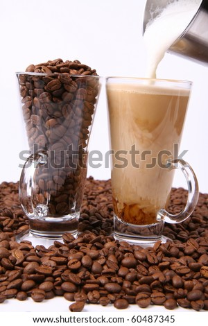Making of caffe latte:glass of coffee with milk being poured into it, with a glass of beans surrounded by coffee beans - stock photo