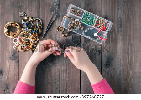 Making of handmade jewellery. Box with beads on old wooden background. Handmade accessories. Top view - stock photo