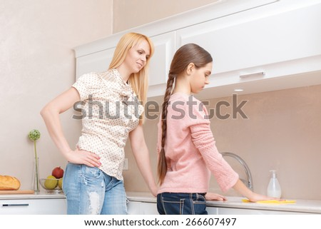 Making order. Young mother supervises how her teen daughter is cleaning the kitchen counter with a cloth - stock photo