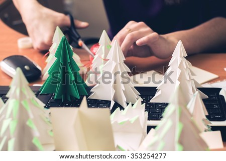 Making origami Christmas trees in the office - stock photo