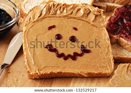 Making peanut butter sandwiches with personality!  Fun smiley face drawn on with jam. Creamy peanut butter with jam on whole grain wheat bread on wood cutting board. Macro with shallow dof. - stock photo