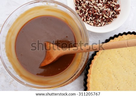 Making pecan pie - stirring the sweet filling with a wooden spoon. Chopped pecans and shortcrust pastry pie crust next to the bowl. - stock photo