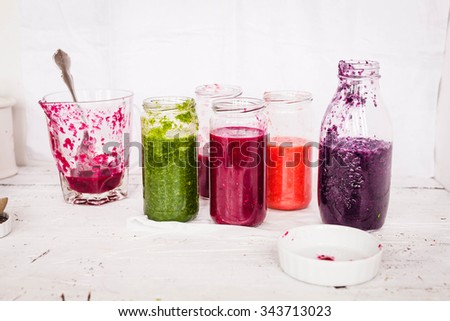 Making purple smoothie recipe concept. Red cabbage, grape, blackberries and pomegranate smoothies in glass jars preparing at home. Colorful rustic image. - stock photo