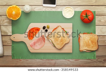 Making sandwich on cutting board at breakfast time top view. - stock photo