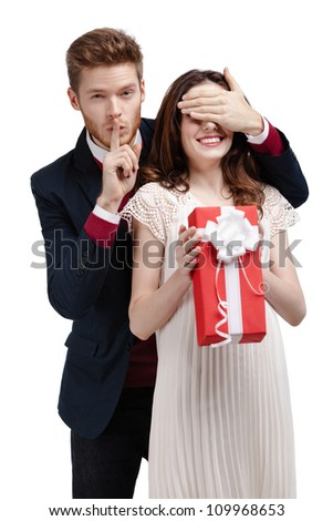Making silence gesture man closes eyes of his girlfriend to give a present, isolated on white - stock photo