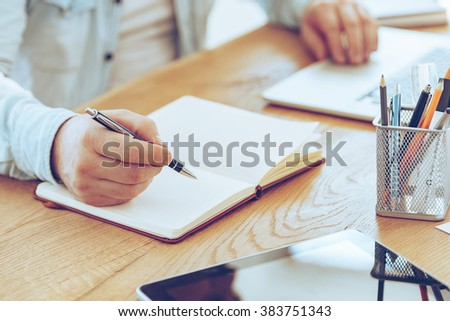 Making some notes. Close-up part of man making some notes in his notepad while sitting at his working place - stock photo