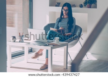 Making some notes. Confident young beautiful woman making notes in notebook while sitting at her working place  - stock photo