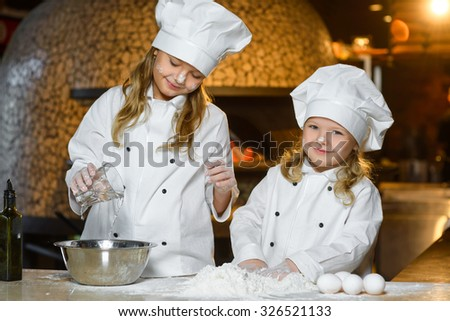 Making the dough for pizza is fun - little chefs playing with flour - stock photo