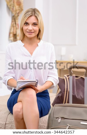 Making the list. Attractive young woman sitting at the edge of bed in her hotel room and writing a list.  - stock photo