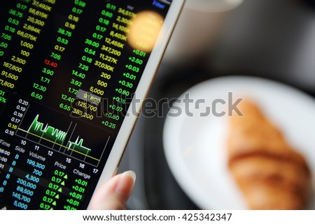 Making trading online on the tablet with business woman hand and croissant - stock photo